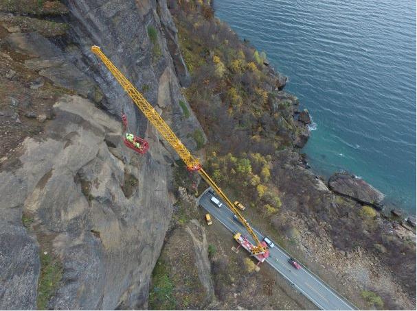 En steinblokk på 70 tonn skal tas ned fra fjellsiden like utenfor Larsbergtunnelen. Jobben gjøres onsdag 26. oktober, i tidsrommet 11-14. Vegen er stengt mens arbeidet pågår, uten mulighet for gjennomslipp av trafikk. Foto: Sørreisa Kran og Transport AS